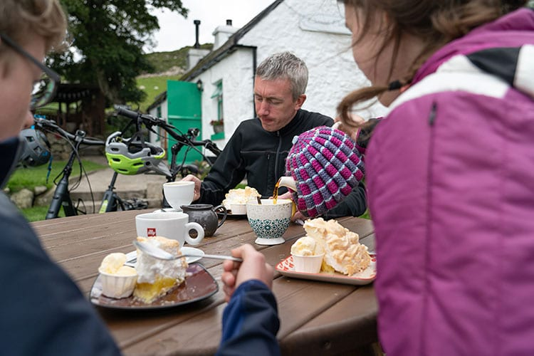 Three mountain bikers drinking tea and eating traybakes at Carrick Cottage, Mourne Mountains