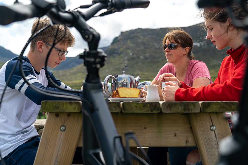 Young teenagers drinking tea and eating traybake with their mother at Meelmore Lodge, Trassey Valley in the Mourne Mountains