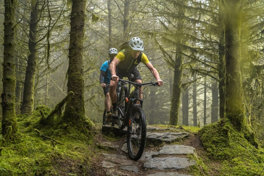 Two mountain bikers descending a rocky step on the Rostrevor Red trail in Kilbroney Forest Park near the Mourne Mountains