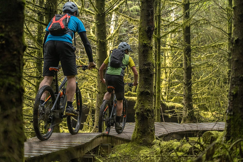 Two cyclists on wooden boardwalk on Rostrevor Red Mountain Bike Trails